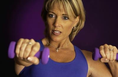 Middle aged woman using weights.