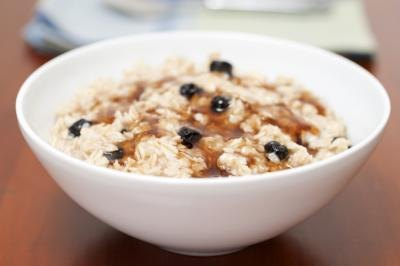 A bowl of oatmeal with maple syrup.
