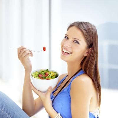 Young woman smiling and eating salad.