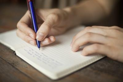 Teenager writing in journal