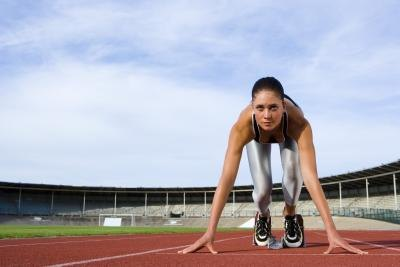 Woman at a starting line of a running track.