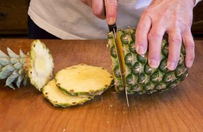 Woman slicing pineapple