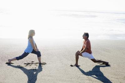 Couple doing lunges on beach