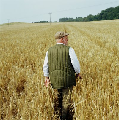 Farmer walking through field of barley