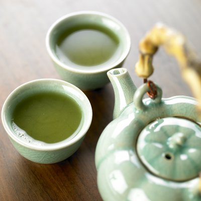 Pot and cups filled with green tea