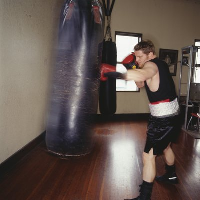 Man punching training bag with boxing gloves.