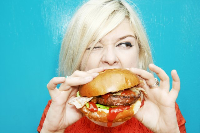 Woman eating a hamburger. Red meat contains a fairly high amount of saturated fat. One 3-ounce hamburger contains 4.5 grams of saturated fat.