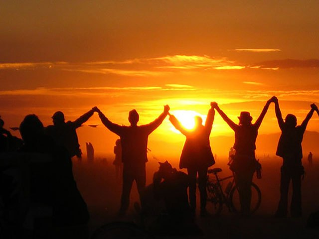 People spontaneously raise their arms together in the air at sunrise near the temple at Burning Man 2008.