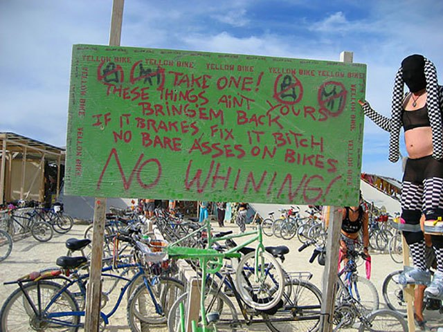 """Take one! These things ain't yours so bring 'em back. No bare asses on bikes! No whining!"" sign at Burning Man 2006."