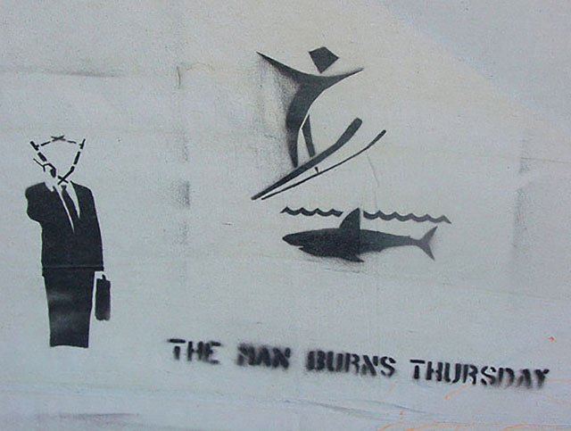 "Stencil graffiti I photographed at Burning Man 2005 shows ""The Man"" with a brief case and cell phone and ""The Man"" jumping the shark."
