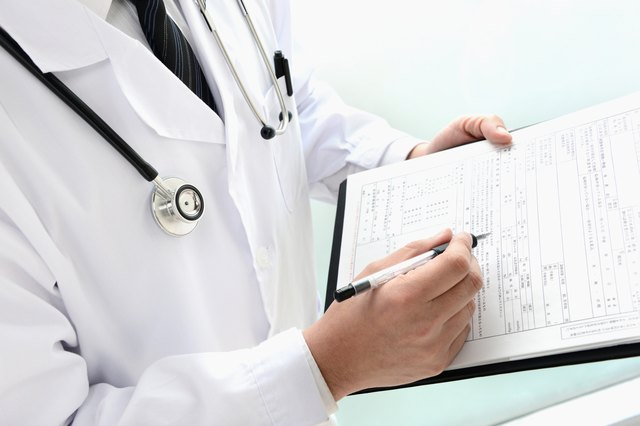 A doctor writes on a medical chart