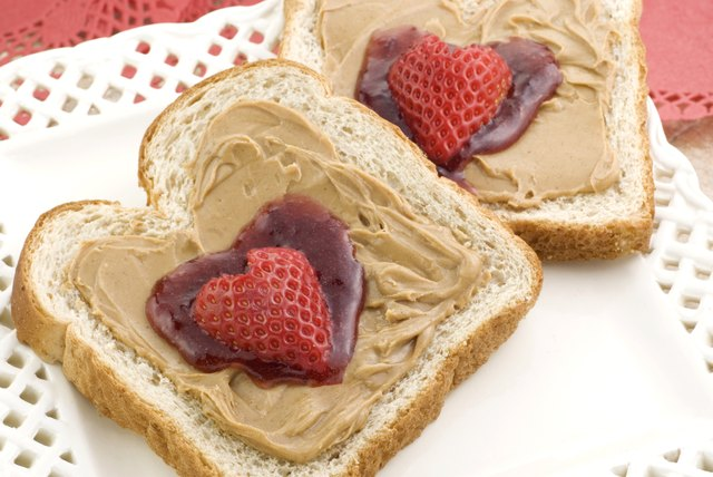 Two slices of whole what bread with peanu butter, jam and a strawberry.