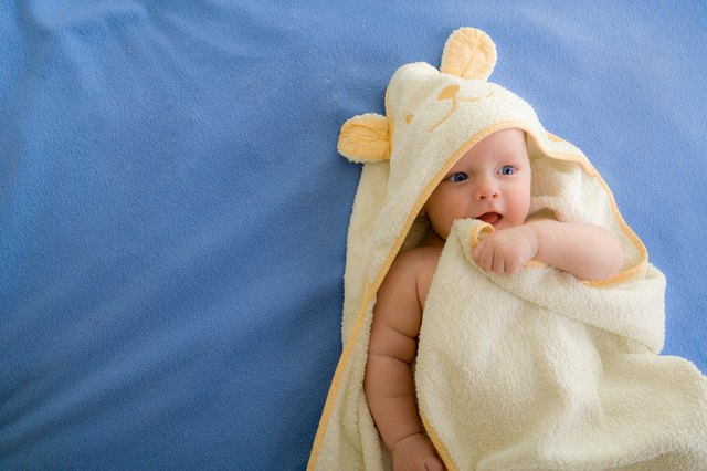 A baby wrapped in a hooded towel lays on a blue blanket.