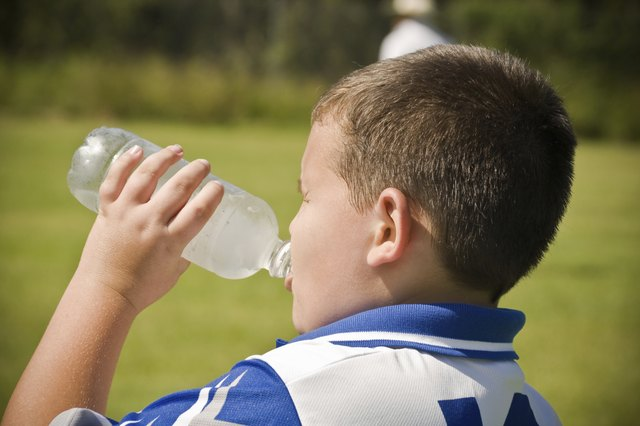young boy takes a break from game and drinks water