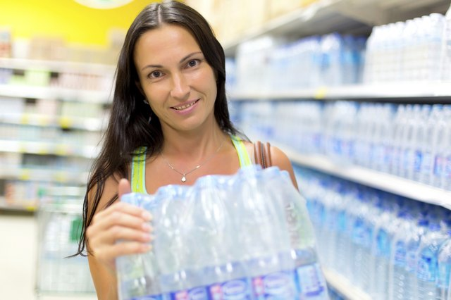 woman holding bottled water in grocery store
