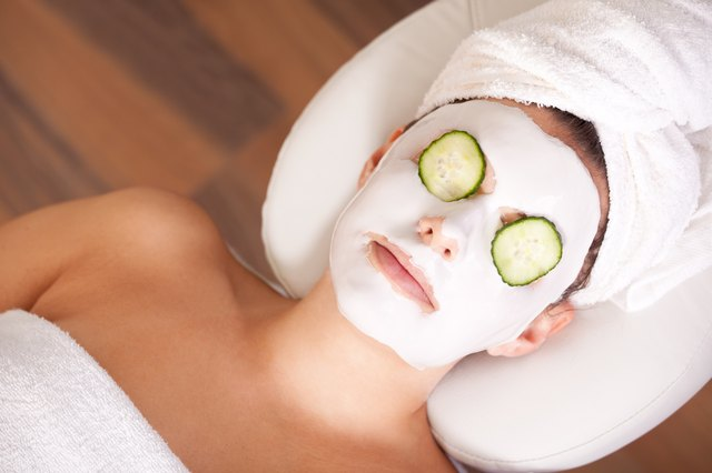 A woman relaxing with a cucumber mask on her face.