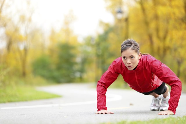 A woman doing pushups outdoors