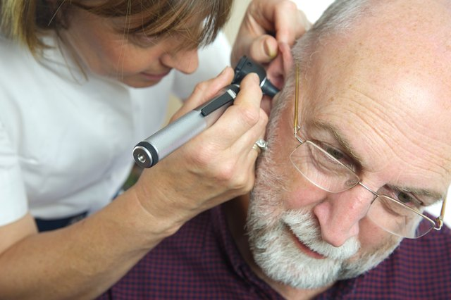A nurse examines the ear of a senior male patient.