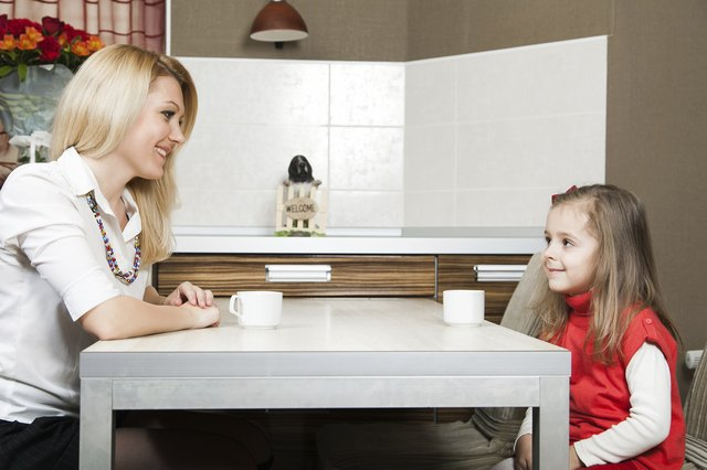 Young mother and daughter talking at a table