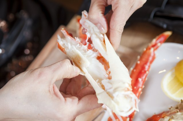 Woman breaking shell of king crab
