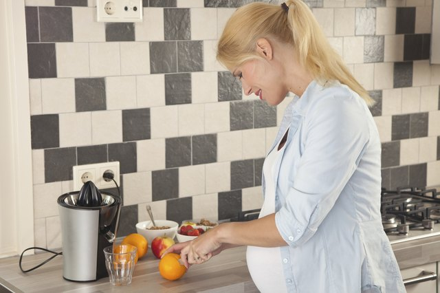pregnant woman cutting oranges for juicer