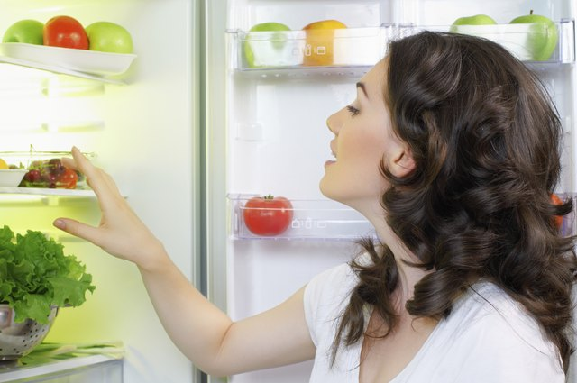 woman looking in fridge for carrots