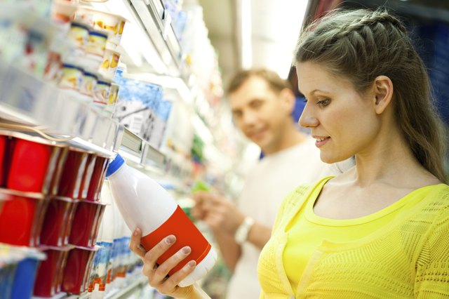 woman looking at milk in grocery store