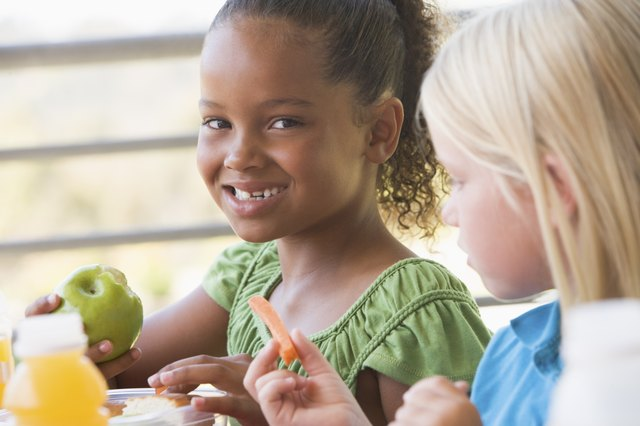 Two school girls eat apples and carrot sticks with lunch.