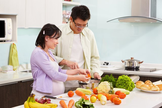 Asian pregnant woman preparing dinner with husband