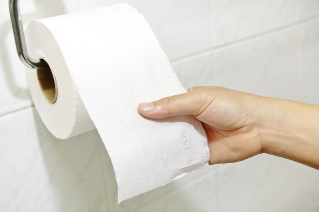 Close-up of a man reaching for toilet paper.