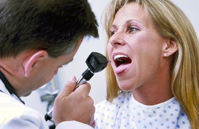 doctor looking at woman's throat