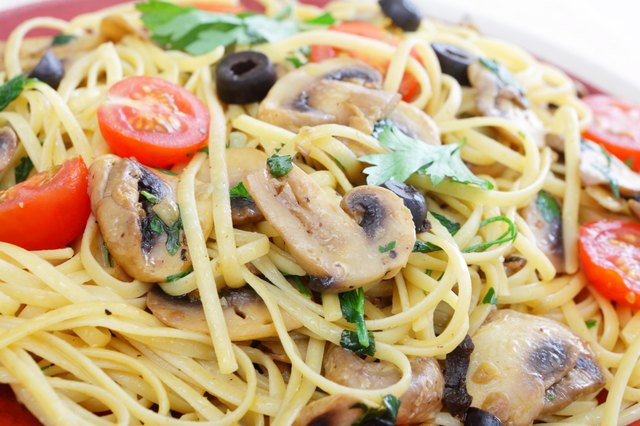 Spaghetti with mushrooms, olives, tomatoes, garlic, basil and parsley