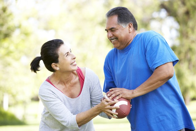 Senior couple exercising with football in park