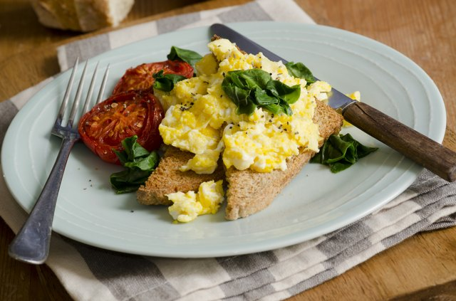A breakfast plate with scrambled eggs on whole wheat toast with tomatoes and fresh basil.