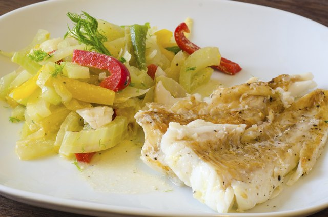 Baked cod with vegetables on a white plate.