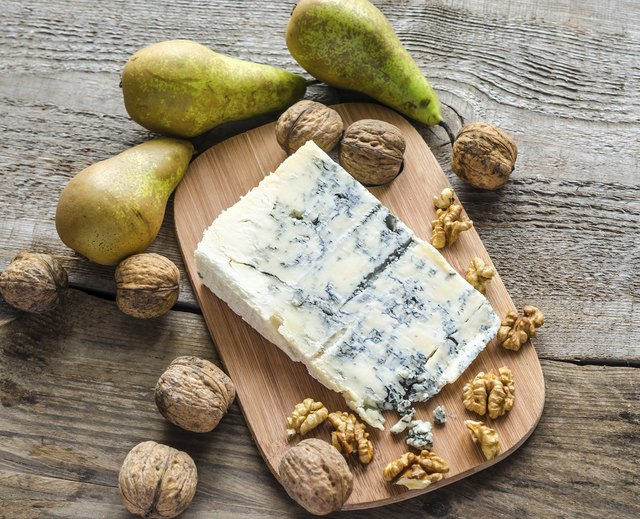 wedge of blue cheese beside fruit and nuts
