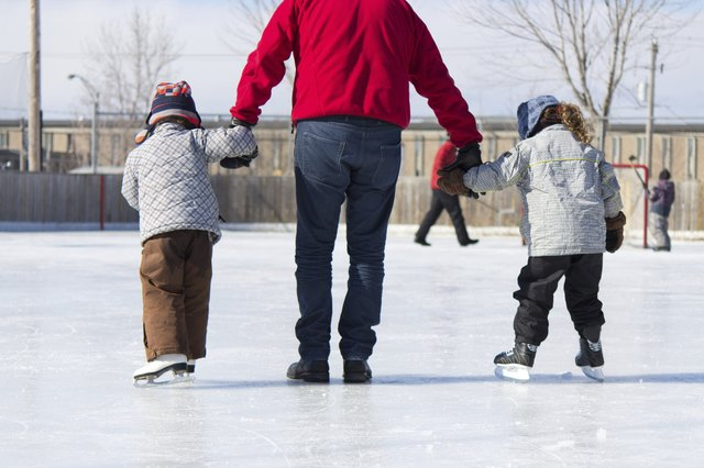 Young children go leisure skating with father