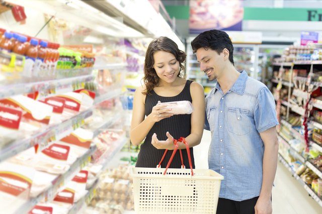 couple looking at mean in grocery store