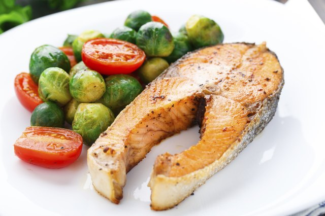 Roasted salmon on a white plate with brusselsprouts and roman tomato slices.