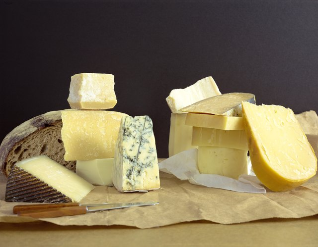 A variety of cheeses on a cutting board.