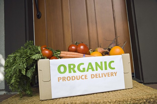 A box of organic produce is delivered and left on the porch.