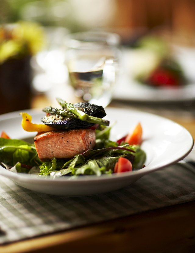 An salmon salad topped with roasted vegetables on a table.