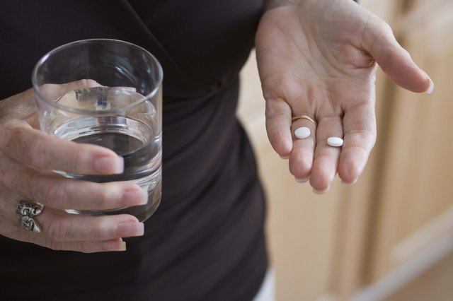 A woman takes two pills with water.