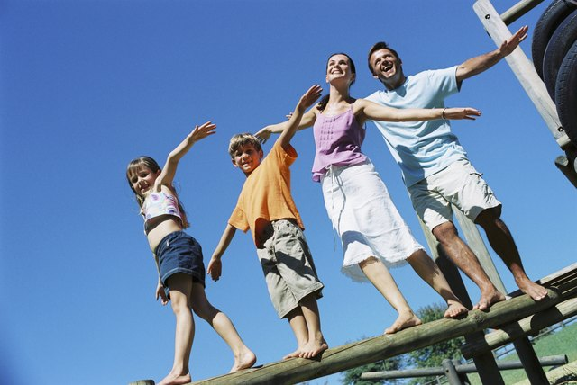 Family outdoors with arms raised up overhead.