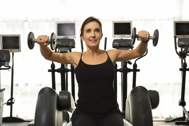 Woman lifting weights at a gym.