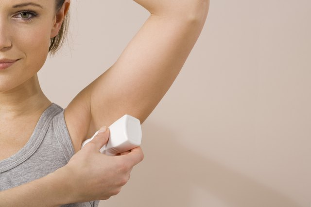 A woman applies deodorant.