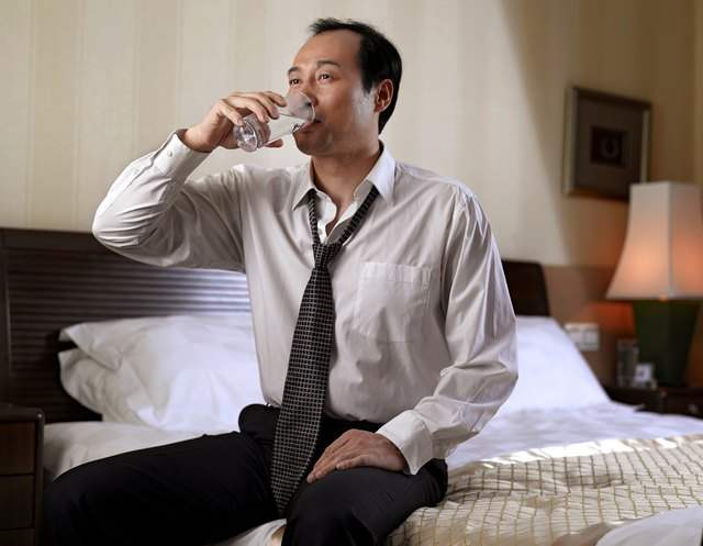 A man drinks a glass of water, while sitting on his bed.