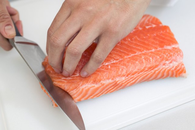 A chef cuts salmon.