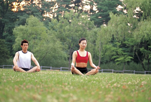 A couple breathing and meditating in the grass.