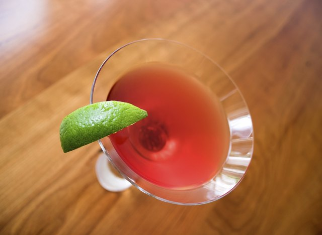 A vodka cosmopolitan cocktail served with a lime wedge on a bar.